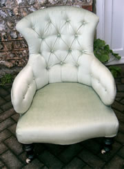 A late Victorian buttoned back chair with turned legs