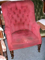 An elegant 19th century buttoned back library chair with turned mahogany legs