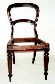 An early Victorian Balloon back dining chair, in Mahogany with a carved rail.